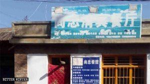 甘粛省白銀市太平店郷、にある回族のレストランの看板にペンキ、テープなどを使った3つの新しいマークが見える。