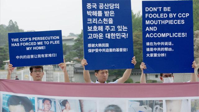 全能神教会信者は看板を手に持ち、中国共産党の残虐行為を非難した。そのうちのひとつにこう書かれている。「中国共産党の迫害によって私は家を追われた」。