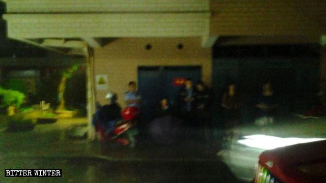 集会所の外で警備する警察官。