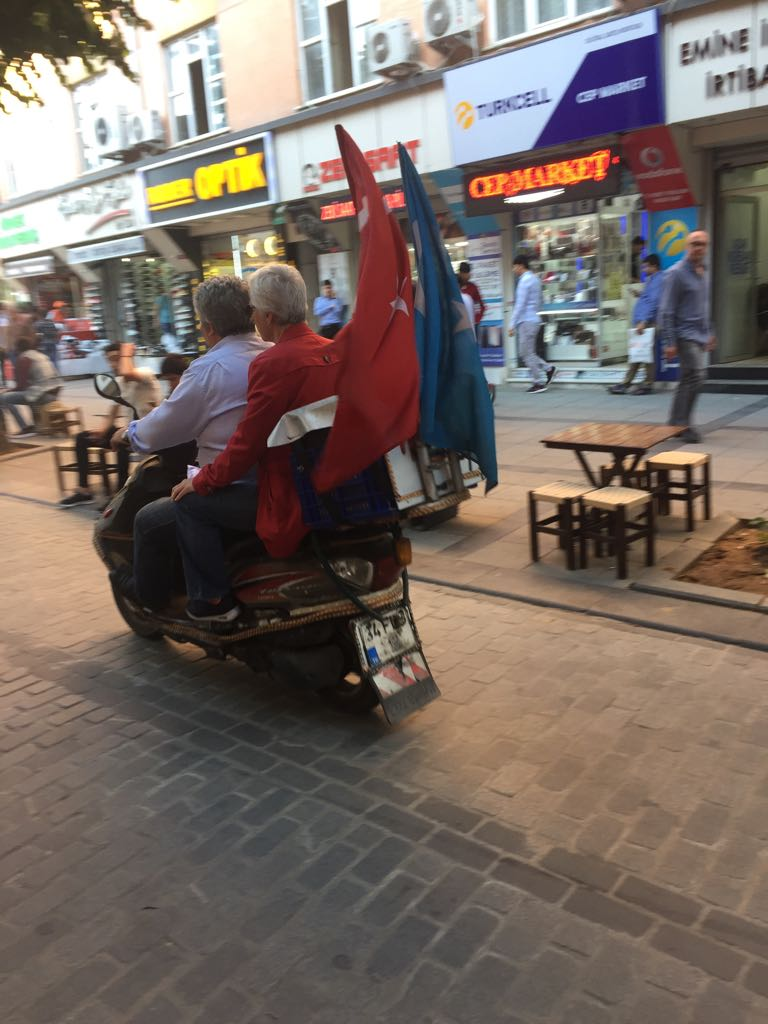 バイクの後ろにトルコとトルキスタンの国旗をなびかせるウイグル族のライダー。