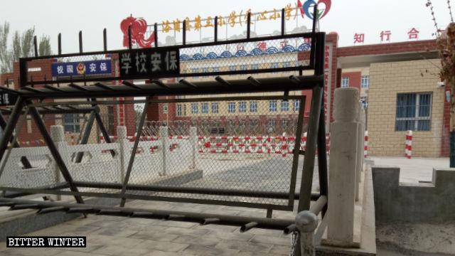 新疆の洛浦県の小学校は、親が「教育による改心」のための強制収容所で勾留されている子供たちを受け入れている。校門は厳重に警備されている。