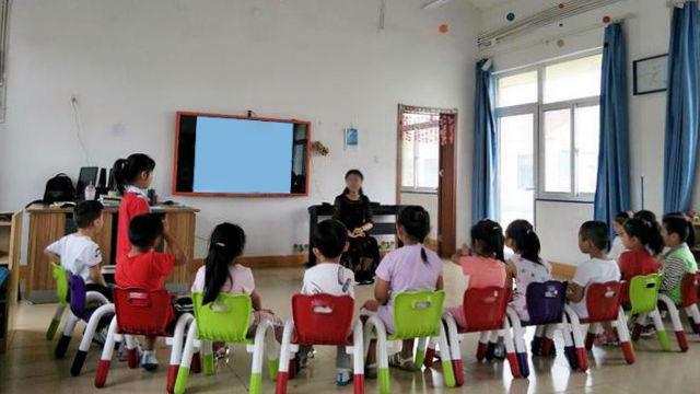 子供たちに話し掛ける幼稚園の教師。