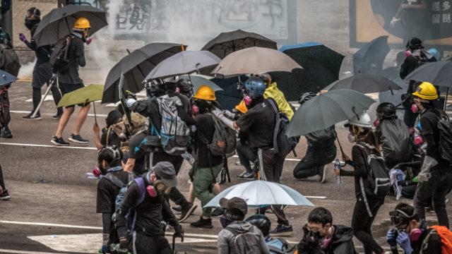 香港の抗議者、報道記者は警察の催涙ガス攻撃に抵抗するため、覆面マスクと傘を必要としている。(Studio Incendo - CC BY 2.0)