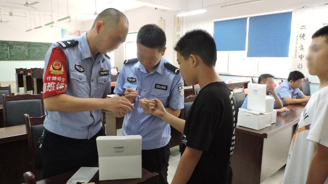 四川省什邡市の公安局所属の警察官が中学生のDNAサンプルを採取している。